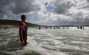 An RNLI lifeguard in the sea at Woolacombe beach, Devon.Lots of people in the water swimming